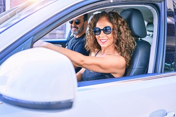 Middle age beautiful couple on vacation wearing sunglasses smiling happy driving car.