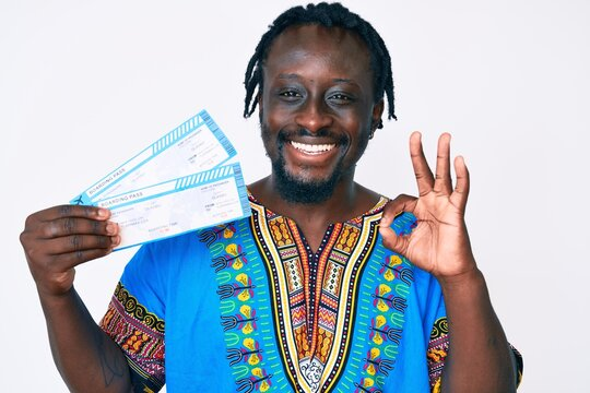 Young african american man with braids wearing ethnic clothes holding airplane boarding pass doing ok sign with fingers, smiling friendly gesturing excellent symbol