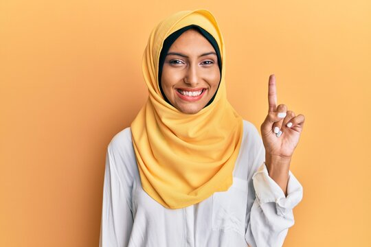 Young brunette arab woman wearing traditional islamic hijab scarf showing and pointing up with finger number one while smiling confident and happy.