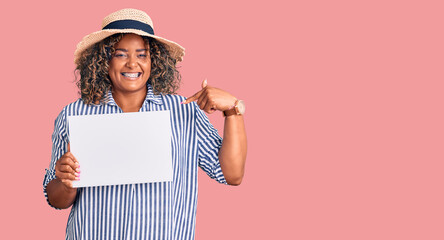 Young african american plus size woman holding cardboard banner with blank space pointing finger to one self smiling happy and proud