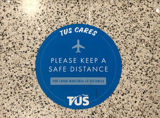 """TUS Cares - Please keep a safe distance"" floor sticker at Tucson International Airport in Arizona"
