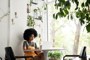 Happy stylish hipster African American female student with Afro hair using laptop computer sitting...