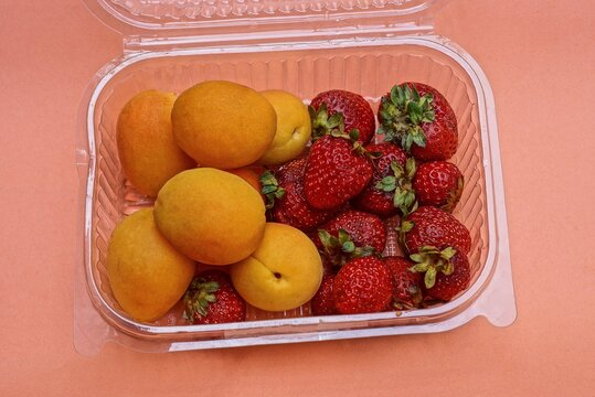 fresh and ripe strawberry and apricot fruits in a plastic box on an orange table