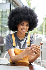 Smiling happy African American young hipster mixed race gen z young woman with Afro hair holding...