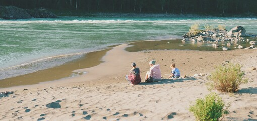 Mother and two children on the beach of Katun river, Altay