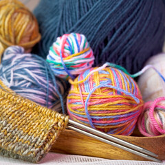 Multi-colored wool for knitting. Knitting needles.