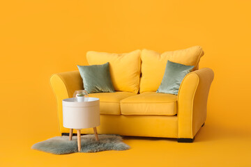 Stylish sofa and table on color background