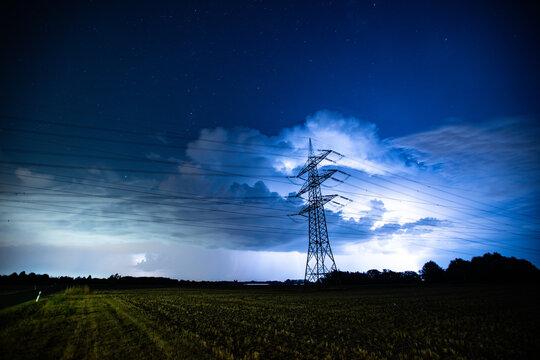 Powerlines in front of a Thunderstorm over a field