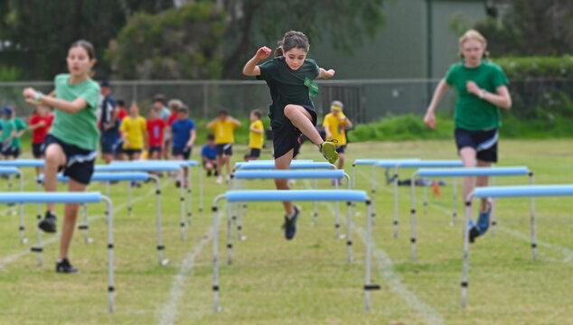 Young girl runs a hurdle