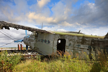 Old-fashioned crashed and abandoned small propeller plane. Airplane graveyard