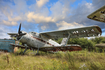 Airplane cemetery in the field against cloudy blue sky