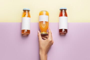 Female hand with bottles of juices on color background