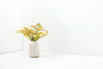 White simple vase with yellow flowers, front view