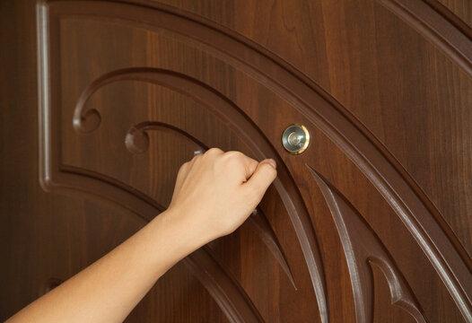 Woman knocks on the house door.