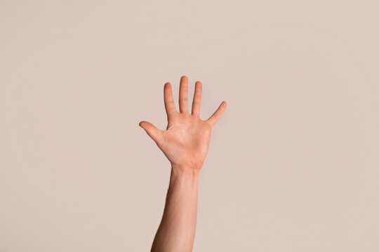 Young guy showing his hand with open palm, gesturing high five on light background, closeup