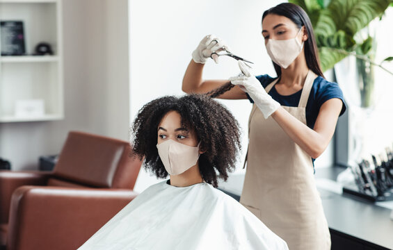 Hairdresser and client at beauty salon both in protective masks