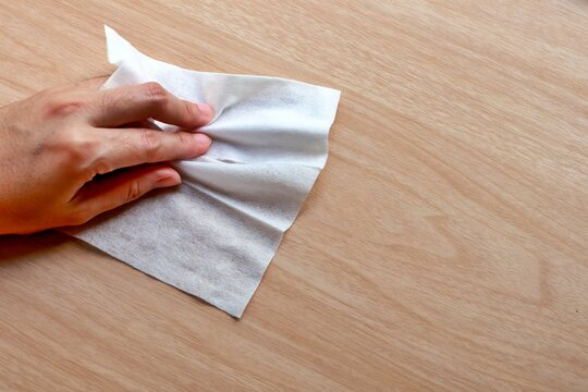 Alcohol clean pad wiping and cleaning wooden table for disinfect virus bacteria, prevent from epidemic of disease during the corona virus outbreak.