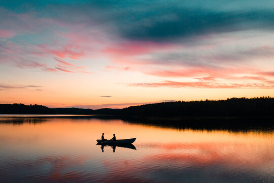 Scenic view of men fishing in Saimaa Lake during sunset