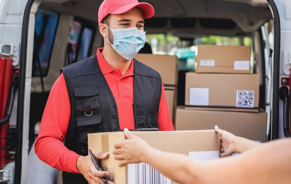 Courier man delivering package with truck while wearing protective face mask for coronavirus prevention - Shipping service and social distance concept - Focus on man worker