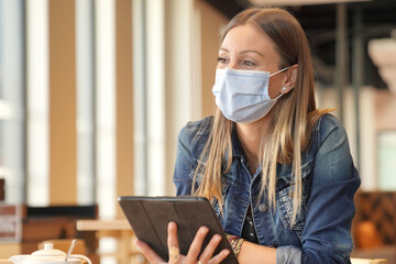 Young woman sitting at coffee shop and working on digital tablet with face mask