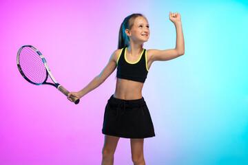 Winner. Little tennis girl in black sportwear isolated on gradient background in neon light. Little...