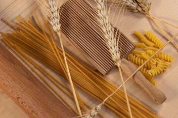 View of various types of pasta on wooden background with ears of wheat.  Mediterranean diet concept
