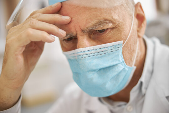 Senior citizen wearing a lab coat and a mask looking tired
