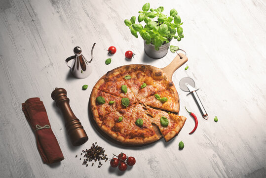 Fresh pizza with tomatoes and basil on a white washed wooden counter. Pepper grinder, pizza cutter and napkin surrounding the pizza.