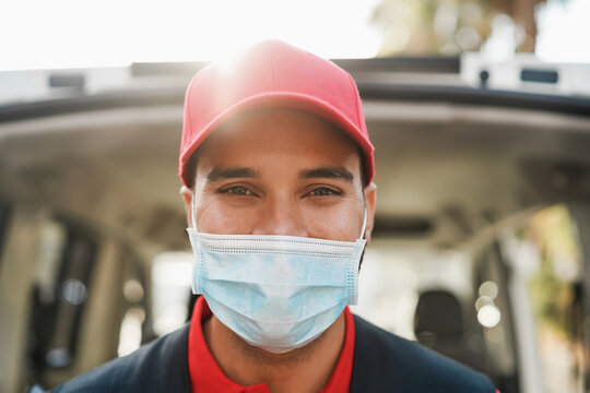 Portrait of delivery man wearing face protective mask for coronavirus spread prevention - Courier person at work during covid 19 pandemic time