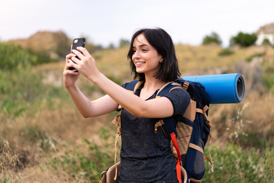 Young mountaineer girl taking a selfie with the mobile with a big backpack at outdoors