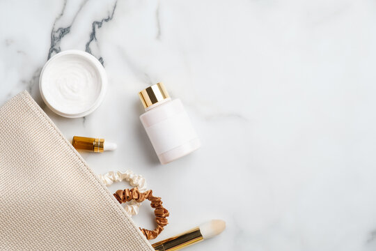 Makeup bag with natural cosmetic products set on marble desk. Flat lay, top view moisturizer cream, body lotion, serum dropper bottle, make-up brush. Skincare concept.