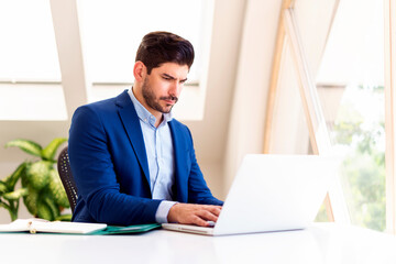 Stressed businessman using laptop while working in the office