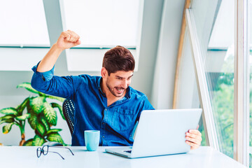 Successful businessman working on laptop at office desk