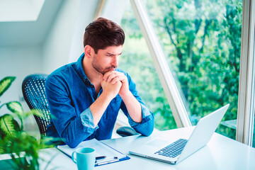 Businessman looking thoughtfully while working on laptop