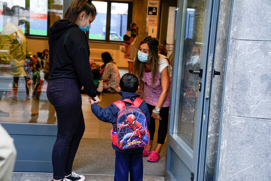 A teacher wearing a protective mask welcomes a pupil on the first day of school after the summer holidays during the coronavirus disease (COVID 19) outbreak, at Colegio Pureza de Maria school in Bilbao