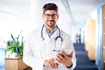 Male doctor using digital tablet while standing on the clinic's foyer