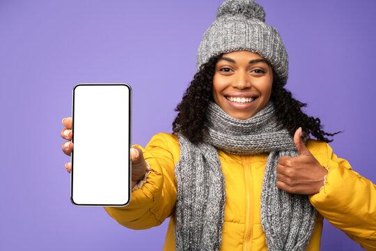 Girl Showing Smartphone Screen Posing Wearing Winter Jacket, Purple Background