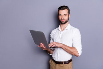 Portrait of his he nice attractive focused skilled brunet guy employer using laptop researching analyzing web market browsing finance report isolated over gray pastel color background
