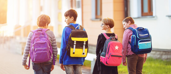 Children with rucksacks standing in the park near school