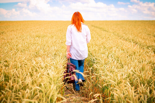 young girl in countryside road near wheat field, summer background