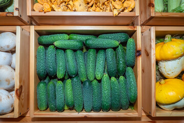 Fresh vegetables in boxes. Cucumbers in a wooden box. Colorful vegetables top view. Sale of vegetables. Food trade. Environmentally friendly product. Vegetarian food.
