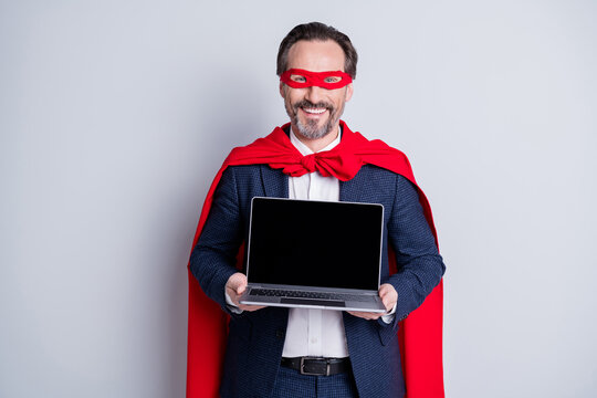 Photo of confident cheerful aged mature business guy super hero costume hold laptop presenting novelty new device model sale price wear suit red face mask cloak isolated grey background