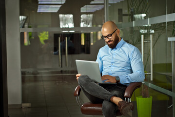 Businessman in a blue shirt sitting in a brown leather chair. Man with laptop in glasses. Bearded office worker at work.