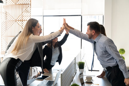 Business team giving high fives in office