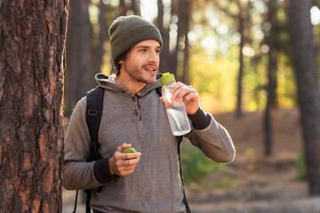 Handsome guy drinking water while walking by forest Wall mural