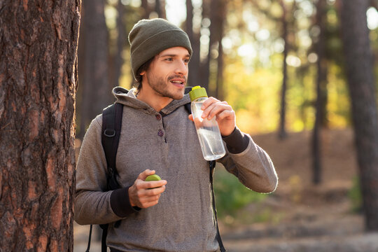 Handsome guy drinking water while walking by forest