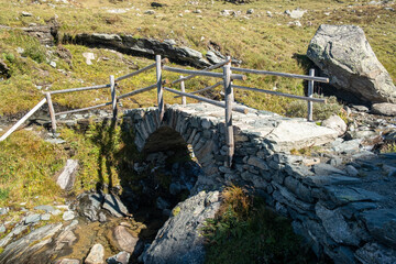 Small stone bridge to cross a stream on a mountain path.
