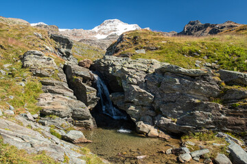 Panoramic view of alpine landscape with a small waterfall.
