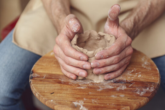 The master creates a white clay product. The master's hands close-up sculpt a clay product using a potter s wheel. The potter teaches his apprentice mastery.