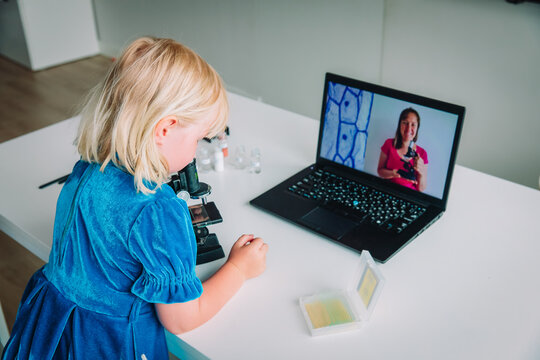 Kid learning remotely. Girl making experiments, looking through microscope during online lesson